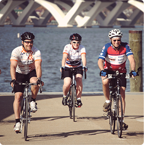 three people biking alongside a river