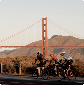 group of bikers biking with Golden Gate Bridge in background