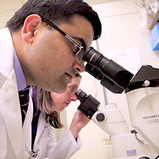 Researcher looking into microscope – Breakthroughs to a Cure