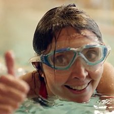 Woman swimming giving thumbs up